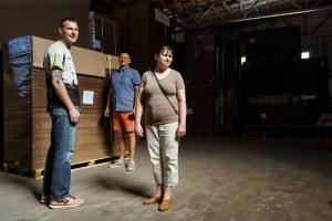 Inga, Ingus un priekšnieks noliktavā stāv pie paletes ar kartonu