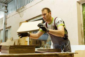 Ingus darbā ar darba cimdiem rokās kārto kartona loksnes