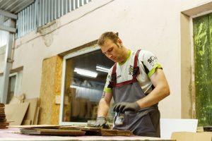Ingus darbā, ar darba cimdiem rokās kārto kartona loksnes