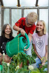 Deniss ar leikanu laista augus siltumnīcā. Fonā mamma ar māsu