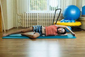 Elīna sporta zālē guļ uz sāna uz paklājiņa