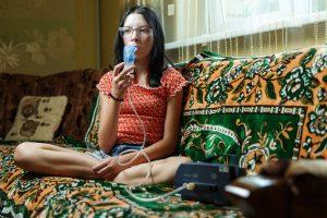 Elīna sēžot dīvānā elpo zāles caur inhalatoru