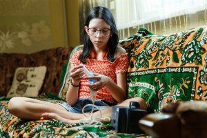 Elīna sēž dīvānā ar inhalatoru rokās