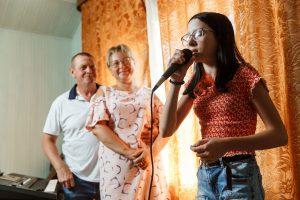 Elīna dzied. Uz viņu noraugās vecāki