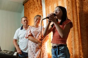 Elīna tur rokās mikrofonu un dzied. Fonā uz viņu noraugās vecāki